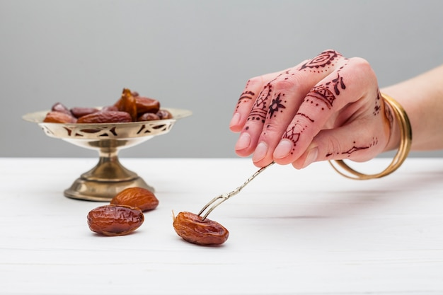 Person with mehndi holding date fruit with fork
