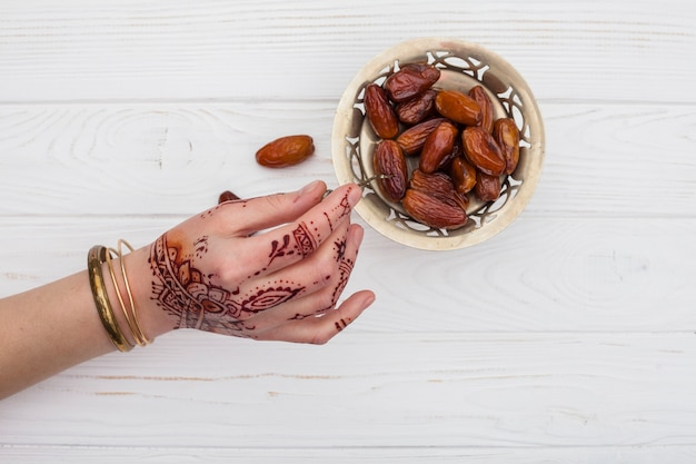 Person with mehndi holding dried date fruit with fork