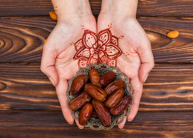 Person with mehndi holding plate with dates fruit