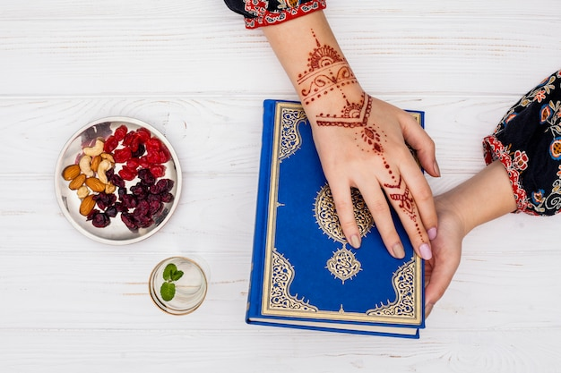 Person with mehndi holding quran near dried fruits