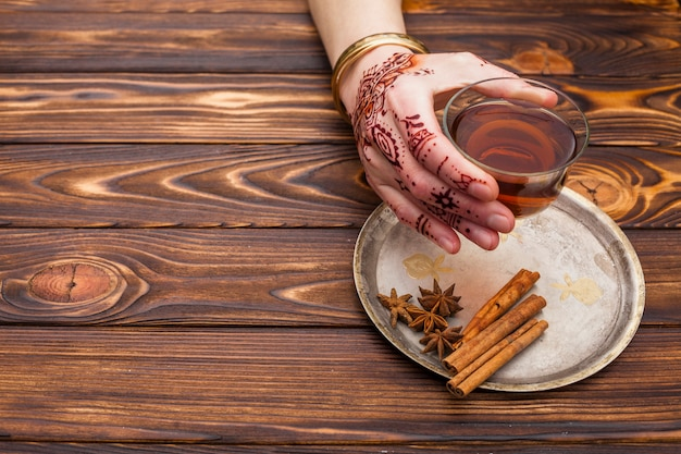 Person with mehndi holding tea cup on table