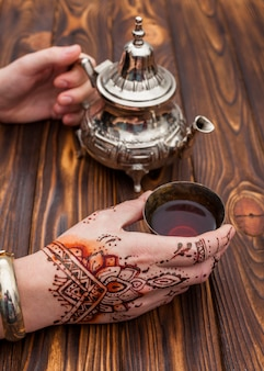 Person with mehndi holding teapot and cup