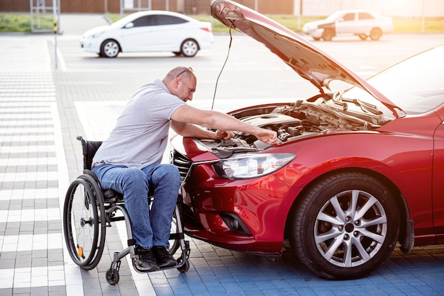 Person with a physical disability check engine his car at parking