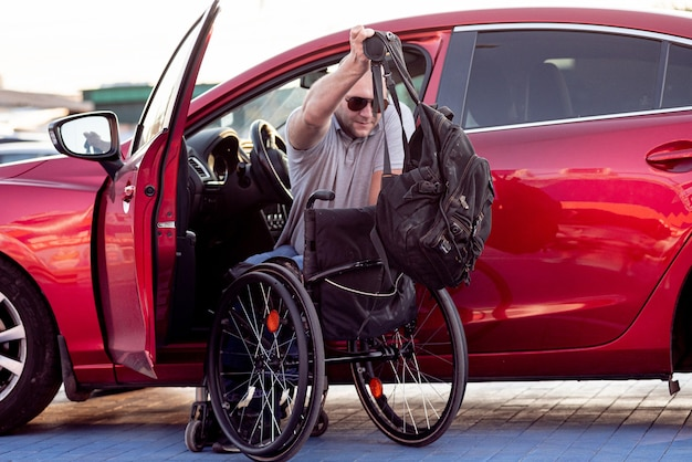Person with a physical disability getting in red car from wheelchair