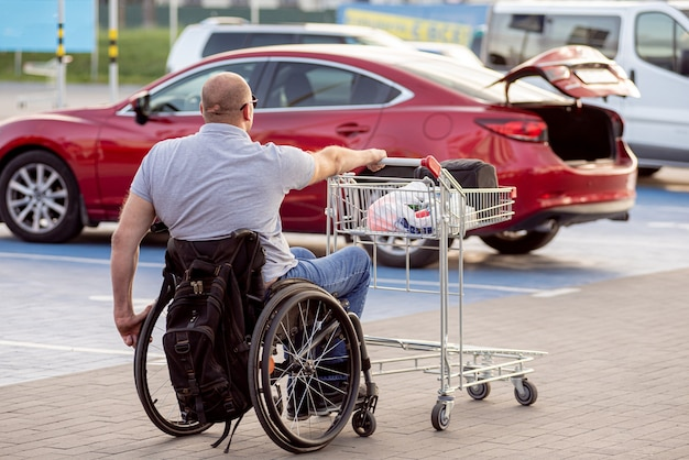 Person with a physical disability pushes a cart towards a car in a supermarket parking lot