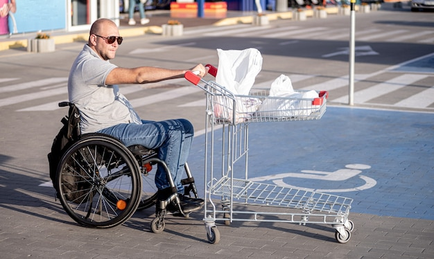 Person with a physical disability pushing cart in front of himself at supermarket parking