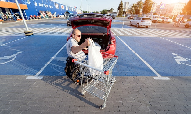 Person with a physical disability puts purchases in the trunk of a car in a supermarket parking lot