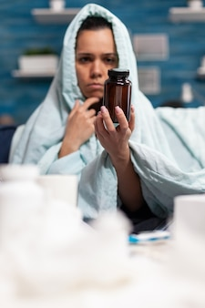 Person with sickness holding bottle of capsules