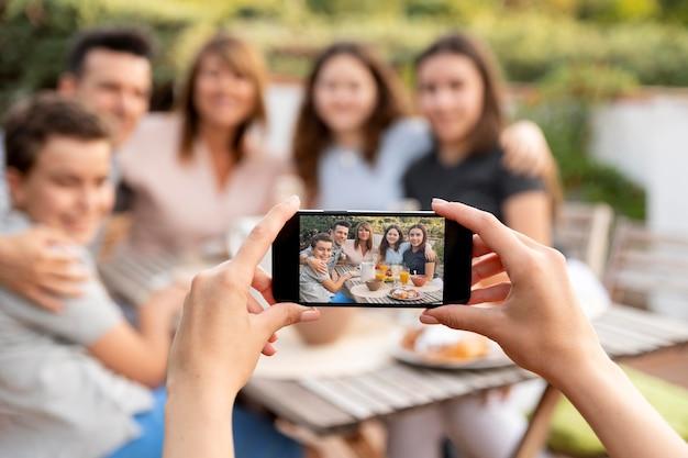一緒に屋外で昼食をとっている家族の写真を撮るスマートフォンを持つ人