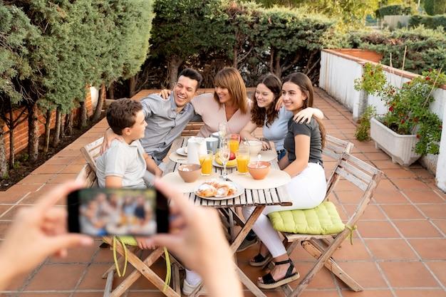 야외에서 함께 점심을 먹는 가족 사진을 스마트폰으로 찍는 사람