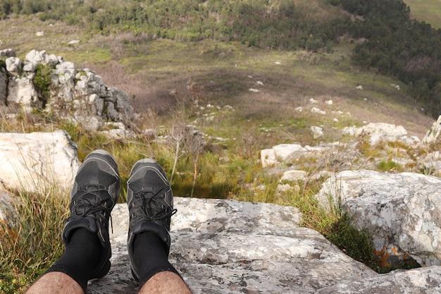 Человек в спортивной обуви сидит на скале и расслабляется