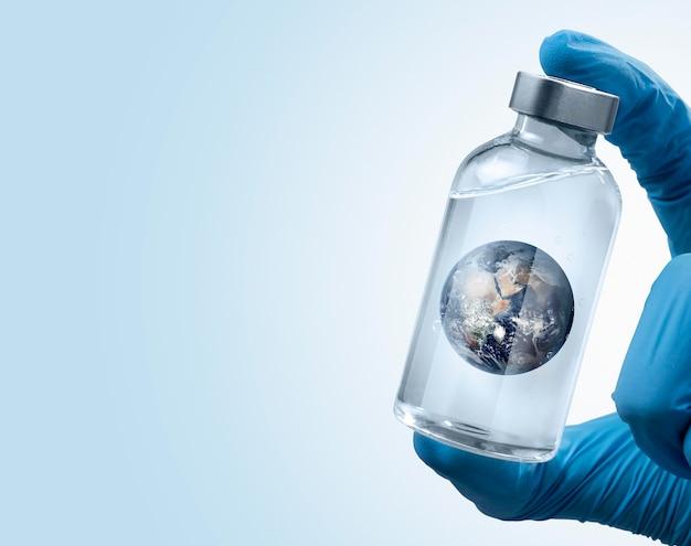 Человек в хирургических перчатках держит землю в бутылке