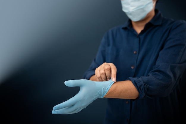 Person with surgical mask on face try to wearing a medical gloves.