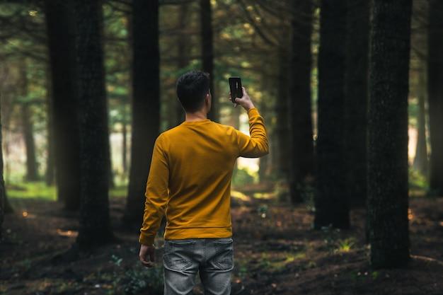 숲에서 모바일로 사진을 찍는 노란색 재킷과 회색 청바지를 입은 사람