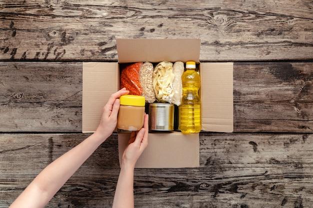 기부를받는 사람이 여자 음식 상자. 여성 자원 봉사 손 나무 테이블에 주식 식품의 식품 항목과 기부 상자를 포장. 음식 배달 개념을 기부하십시오. 기부 식료품 통조림.
