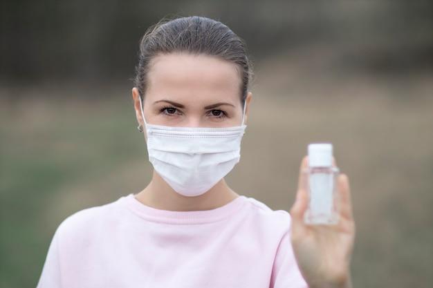 Лицо, женщина, показать дезинфицирующее средство, портативный флакон для дезинфекции рук, девушка в защитной маске на лице. дезинфекция, дезинфекция рук от коронавирусов, вирусных бактерий. пандемия ковид-19