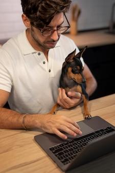 ペットの犬と一緒に家で働く人