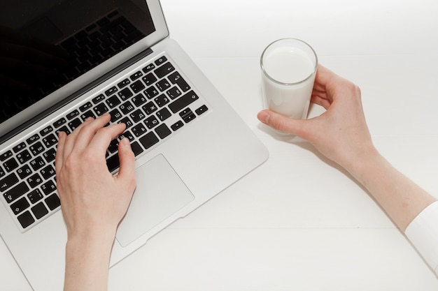 Person working on laptop next to a glass of milk