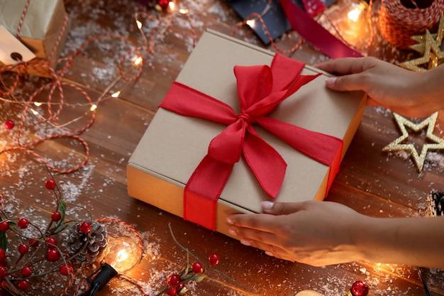 Человек, упаковывающий рождественский подарок