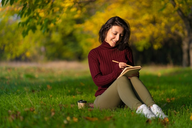 A person write notes sitting on a lawn in an autumn park