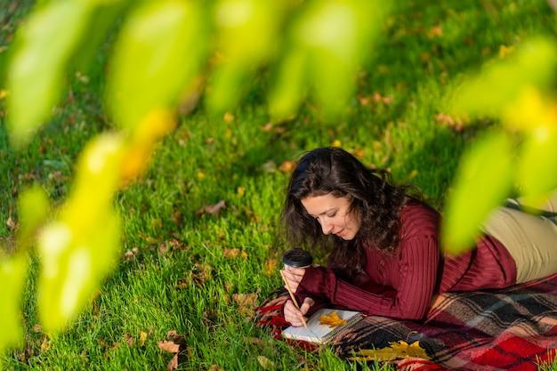 사람은 가을 공원의 잔디밭에 누워 메모를 씁니다. 자신과의 고독.