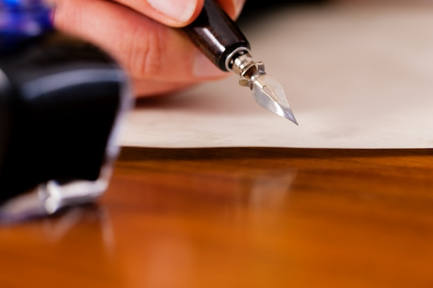 Человек, пишущий письмо с ручкой и чернилами
