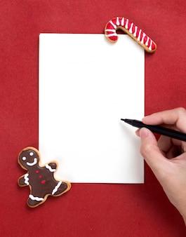 おいしいクリスマスの自家製クッキーで手紙を書いている人