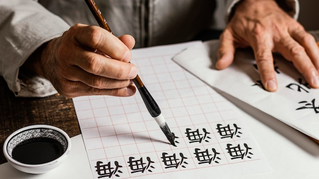 Person writing chinese symbols on white paper