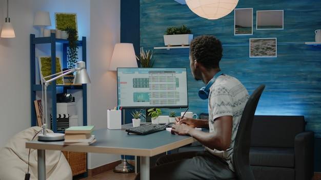 Человек, пишущий данные о криптовалюте на ноутбуке