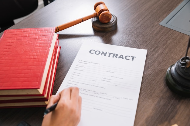Person writing in document at table with books and gavel