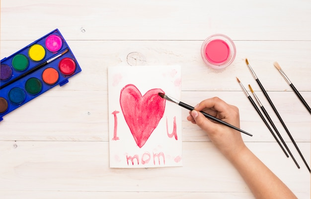 Person writing i love you mom with paint brush