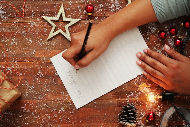 Person writing letter on wooden table with christmas decoration