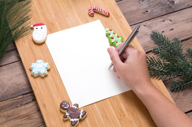 自家製クッキーでクリスマスカードに書いている人