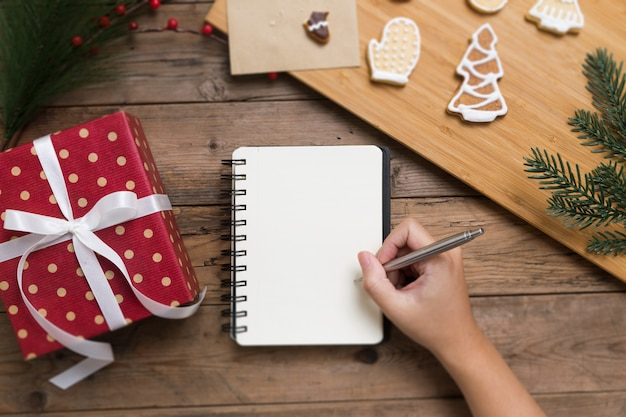 Person writing on open notebook with gift box and tasty christmas homemade cookies