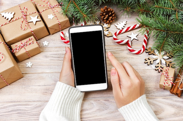 Person writing in opened smartphone on rustic wooden table covered with christmas decoration