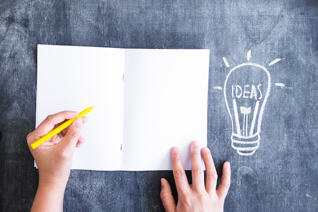 A person writing on paper with yellow crayon and drawn light bulb on chalkboard