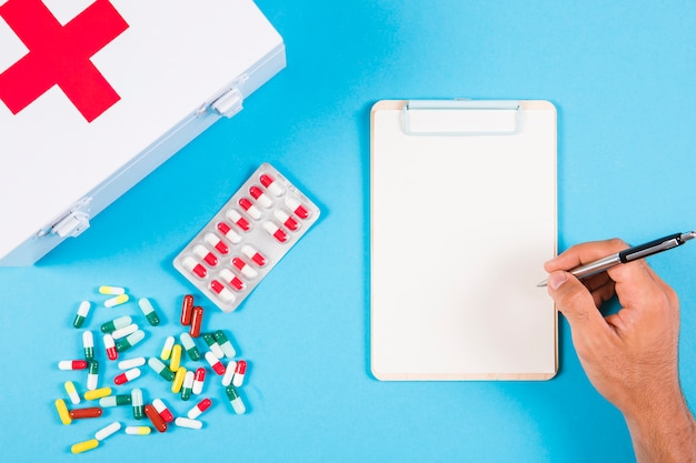 A person writing prescription on clipboard with first aid kit and capsules on blue background