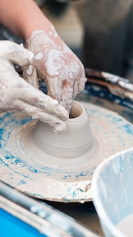 Персона создает кувшин из глины в керамике.