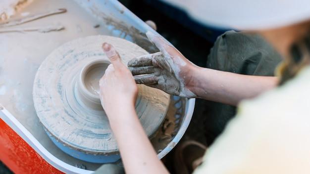 Персона аккуратно лепит глиняную фигурку в гончарной посуде.