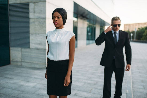 Personal bodyguard in sunglasses and black business woman.