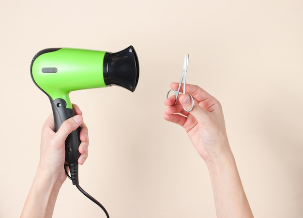 Personal care, beauty concept. female hands holding nail scissors and hairdryer on beige.