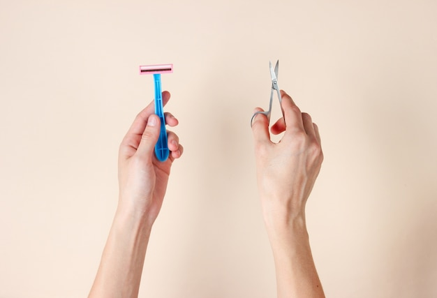 Personal care, beauty concept. female hands holding a toothbrush and nail scissors on beige.