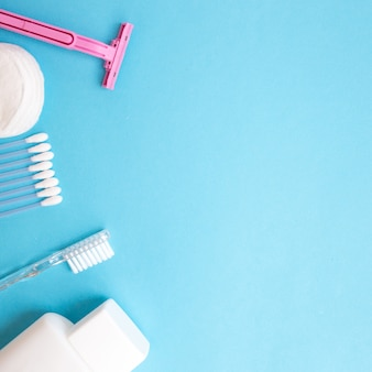 Personal care products. white bottle, razor, ear sticks, cotton pads, toothbrush on blue b