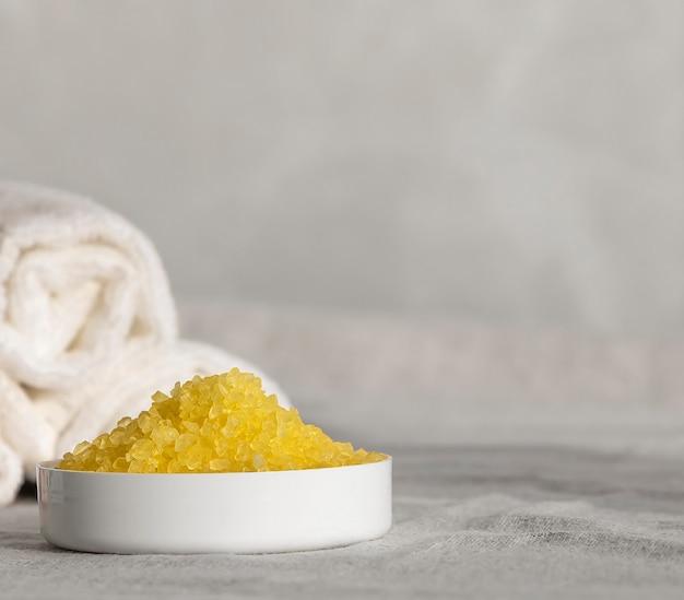 パーソナルケアトリートメント。柑橘系バスソルト、レモンエッセンシャルオイル、レモン、手作り天然石鹸、リネンの背景。