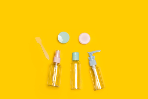 Personal care trip set reusable bottles on a yellow background
