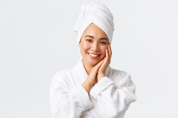개인 관리, 여성 미용, 목욕 및 샤워 개념. 수건에 아름 다운 행복 아시아 여자와 목욕 가운 부드럽게 얼굴을 만지고, 하얀 치아 미소, 피부 관리 및 위생 제품의 프로 모션의 근접.