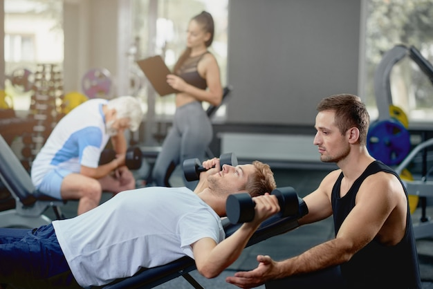 Personal coach helping guy doing exercises lying with dumbbells in gym.