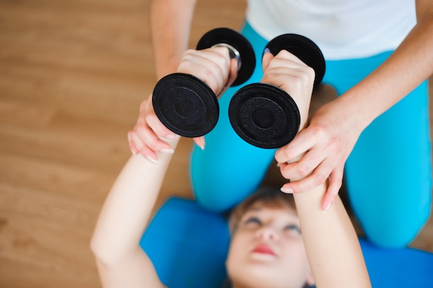 Personal coach helping woman to do exercises with dumbbells in gym.