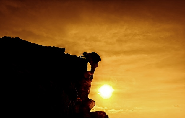 Personal development. business success and goal concept. silhouette climber on the cliff.