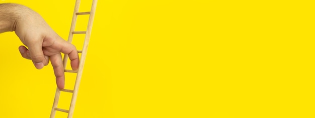Personal development, career growth and leadership concept. male fingers climbing upstairs on yellow wall